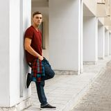 Young stylish man in stylish red t-shirt in a plaid trendy shirt in fashionable blue jeans in sneakers posing outdoors. Near a white vintage building on a stock photo