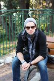 Young stylish man sitting on a bench Royalty Free Stock Images