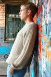 Young stylish man stand near graffiti brick wall. Stock Photo