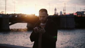 Young stylish man standing on the embankment place near the river and using the smartphone technology on sunset. Male surfing the Internet, spending leisure stock footage