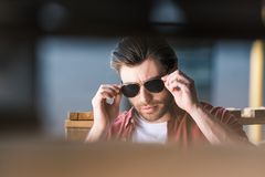Young stylish man standing near wooden pallets and adjusting. Sunglasses stock photography