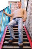 Young stylish man stay on stairs near brick wall. Young stylish man with blonde hair stay on stairs near brick wall royalty free stock image