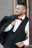Young stylish man in a suit. Portrait of the groom. The groom is holding his jacket on his shoulder, side view Royalty Free Stock Photography