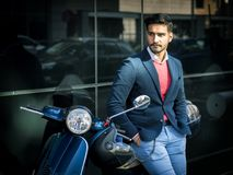 Trendy man by scooter in city Stock Photo