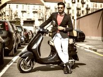 Trendy man by scooter in city Stock Photography