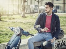 Trendy man by scooter in city Royalty Free Stock Photos