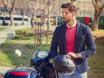 Trendy man by scooter in city Stock Image