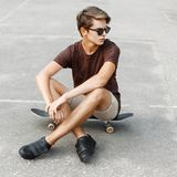 Young stylish man in sunglasses sitting on a skateboard.  Stock Image