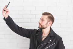 Young stylish man takes selfie on smartphone on white background. royalty free stock photography