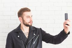 Young stylish man takes selfie on smartphone on white background. royalty free stock image