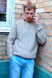 Young stylish man talk on mobile phone. Young stylish man talk on mobile phone near brick wall Stock Image