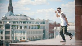 Young stylish man with tattoos freestyle dancing on the stand - centre of the city on the background. Mid shot stock video footage