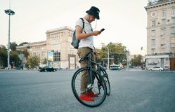Young stylish man texting on the phone while standing aside bike stock photography