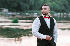 Young stylish man in a waistcoat, horizontal portrait of the groom, portrait on a background of nature, the river and the pier Stock Image