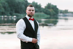 Young stylish man in a waistcoat, horizontal portrait of the groom, portrait on a background of nature, the river and the pier royalty free stock photo