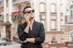 Outdoors leisure. Young man and sunglasses in suit standing on city street answering phone call looking up smiling royalty free stock photos