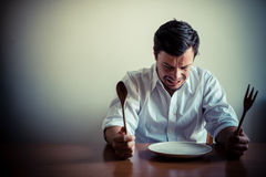 Young stylish man with white shirt eating in mealtimes Royalty Free Stock Photos