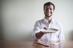 Young stylish man with white shirt eating in mealtimes Royalty Free Stock Image