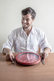 Young stylish man with white shirt eating red clock Royalty Free Stock Photo