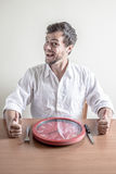 Young stylish man with white shirt eating red clock Royalty Free Stock Images