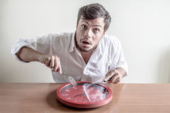 Young stylish man with white shirt eating red clock Royalty Free Stock Image