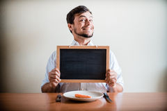 Young stylish man with white shirt holding blackboard Stock Images