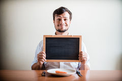 Young stylish man with white shirt holding blackboard Stock Photo