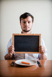 Young stylish man with white shirt holding blackboard Stock Image
