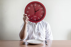 Young stylish man with white shirt holding red clock Stock Photo