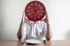 Young stylish man with white shirt holding red clock Stock Photography