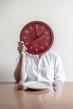 Young stylish man with white shirt holding red clock Royalty Free Stock Images