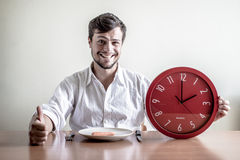 Young stylish man with white shirt holding red clock Royalty Free Stock Image