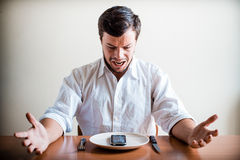 Young stylish man with white shirt and phone on the dish Royalty Free Stock Images