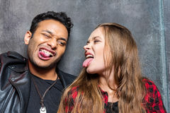 Young stylish man and woman sticking tongues out. Portrait of young stylish men and women sticking tongues out Stock Photos