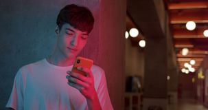 Young Stylish Millenial Boy in White T-Shirt Using his Smartphone for Chatting, Typing Messages while Standing at