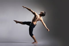 Young and stylish modern ballet dancer. On grey background Royalty Free Stock Image