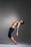 Young and stylish modern ballet dancer. On grey background Stock Photos