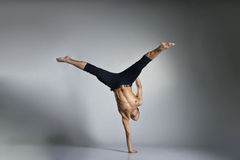 Young and stylish modern ballet dancer. On grey background Stock Photo