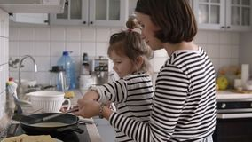 Young stylish mother helps daughter turn the pancake with a shovel and having fun while cooking together in kitchen at. Home with two children stock footage