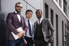 Young stylish multiethnic businessmen in formalwear posing outdoors. Business team meeting Royalty Free Stock Images