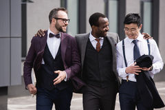 Young stylish multiethnic businessmen in formalwear walking outdoors. Business team meeting stock photo