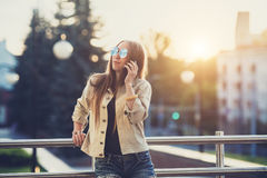 Young stylish pretty Woman, hands holding a phone. Sunset background, Sunny day,good weather, sunglasses, cool. Young stylish pretty Woman, hands holding a phone royalty free stock photography