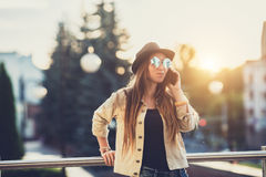 Young stylish pretty Woman, hands holding a phone. Sunset background, Sunny day,good weather, sunglasses, cool. Young stylish pretty Woman, hands holding a phone royalty free stock images