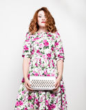 Young stylish red-haired woman with curly hair and pretty face holding a shiny bag. Royalty Free Stock Photography