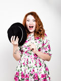 Young stylish red-haired woman with curly hair and pretty face holds a black hat. expresses different emotions Stock Photography