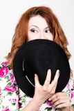 Young stylish red-haired woman with curly hair and pretty face holds a black hat. expresses different emotions Royalty Free Stock Image