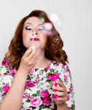 Young stylish red-haired woman with curly hair and pretty face posing and blow bubbles. expresses different emotions Stock Image