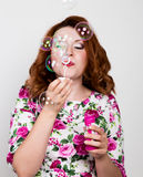 Young stylish red-haired woman with curly hair and pretty face posing and blow bubbles. expresses different emotions Royalty Free Stock Images