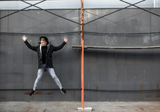 Young stylish redhead man in trendy outfit have fun and jumping against urban wall outdoors. Stock Photos