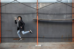 Young stylish redhead man in trendy outfit have fun and jumping against urban wall outdoors. Royalty Free Stock Images